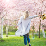 Happen woman walking into blooming cherry trees