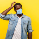 Portrait of uncertain young man with surgical medical mask looking up, scratching head while thinking with confused puzzled face.