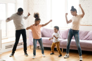 Family with children dancing in modern living room